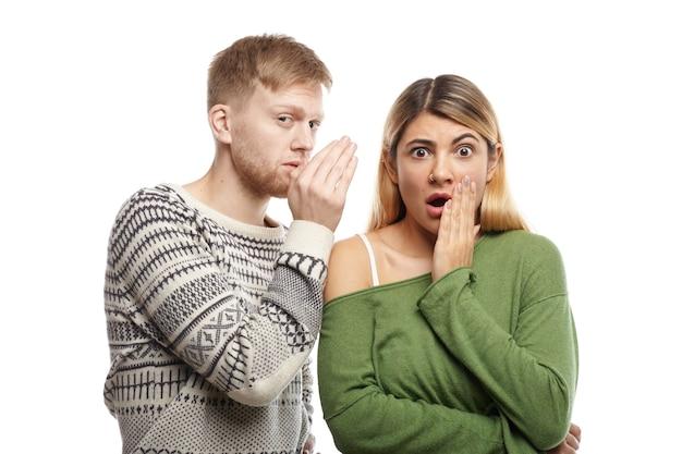 Attraente giovane maschio con la barba lunga che condivide segreti o sussurra pettegolezzi nell'orecchio della sua ragazza stupita, che sta fissando con la bocca spalancata, scioccata da informazioni inaspettate Foto Gratuite