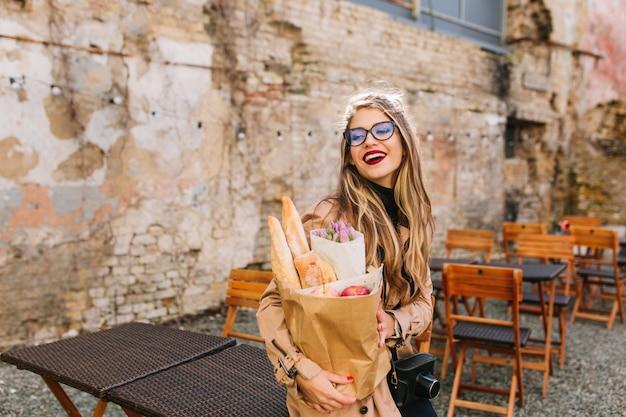 魅力的な若い女性は食べ物の買い物の後屋外カフェに来て、目をそらします。ベーカリーバッグと紫の花の花束を保持している古い壁の前でポーズをとって大きなメガネでスタイリッシュな金髪の女の子。 無料写真