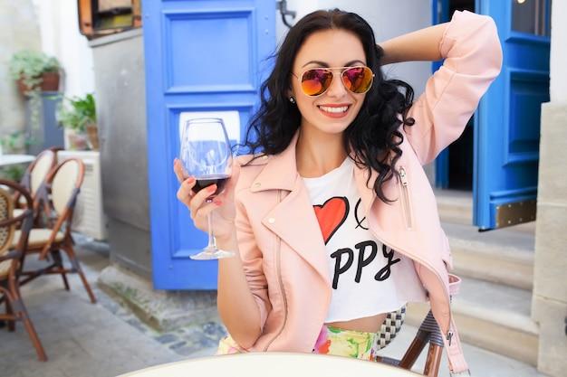 Привлекательная молодая женщина пьет вино на летних каникулах, сидя в уличном кафе города в крутом наряде Бесплатные Фотографии