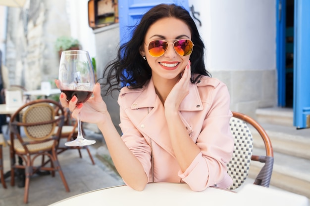 Attraente giovane donna che beve vino in vacanza estiva seduto nel caffè della strada della città in abito fresco Foto Gratuite