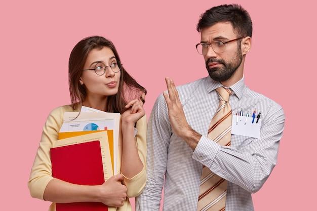 Attraente giovane donna flirta con un bel collega maschio, trasporta libri e documenti Foto Gratuite