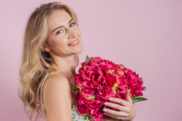 An attractive young woman holding beautiful red flowers against pink backdrop Free Photo