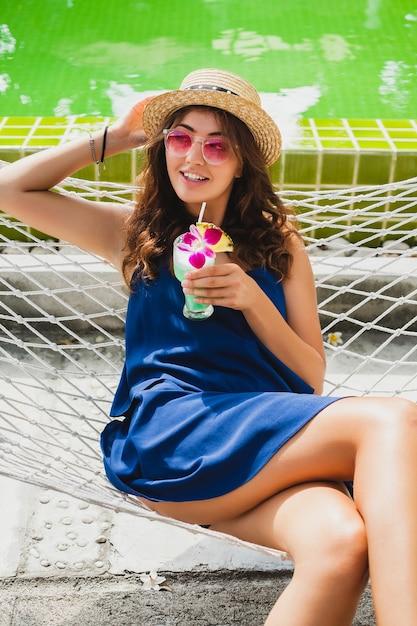 青いドレスと夏のスタイルの衣装でハンモックに座って、パーティー気分で幸せな笑顔で休暇中にアルコールカクテルを飲んでピンクのサングラスを着て麦わら帽子の魅力的な若い女性 無料写真