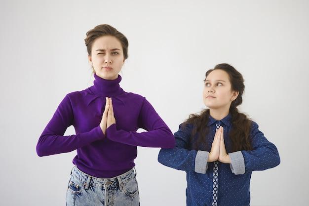 Привлекательная молодая женщина в водолазке и джинсах практикует медитацию в студии со своей дочерью или маленькой сестрой Бесплатные Фотографии