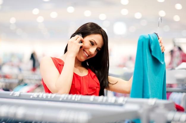 ショッピングで電話で魅力的な若い女性 無料写真