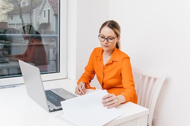魅力的な若い女性はデジタルノートパソコンの前でドキュメントを検索 無料写真