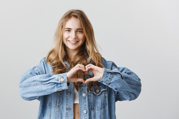Привлекательная молодая женщина показывает жест сердца, чтобы выразить симпатию, сочувствие или любовь Бесплатные Фотографии