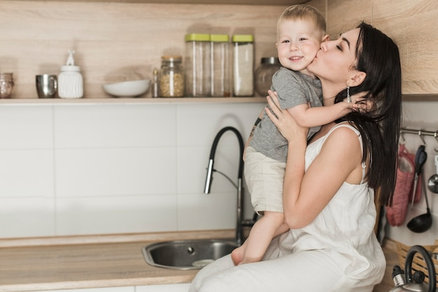 An attractive young woman sitting on kitchen counter loving her son Free Photo