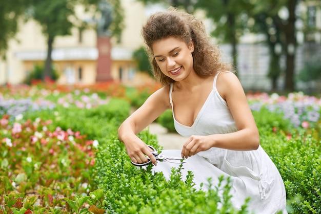 Giovane donna attraente che sorride felicemente tagliando tagliando i cespugli al suo stile di vita lavorante vivente di hobby di cura di giardinaggio del giardiniere del copyspace del giardino. Foto Gratuite