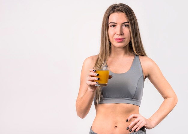 Attractive young woman in sportswear with glass of juice Free Photo