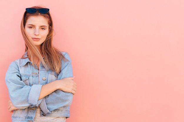 An attractive young woman standing against peach background Free Photo