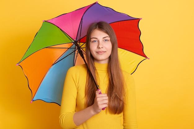 Привлекательная молодая женщина, стоящая под разноцветным зонтиком и в желтом джемпере Бесплатные Фотографии