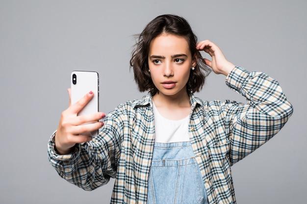 Attraente giovane donna prendendo selfie con il telefono Foto Gratuite