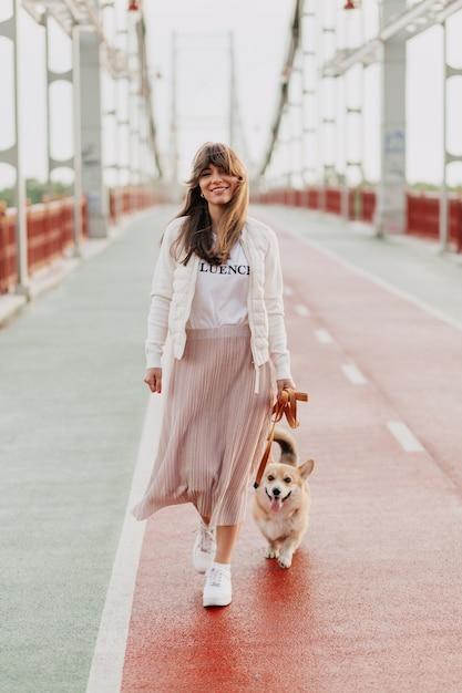 Attraente giovane donna che cammina corgi all'aperto Foto Gratuite