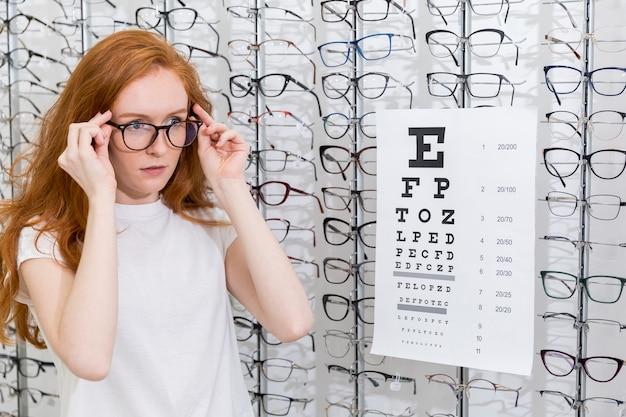 Очки привлекательной молодой женщины нося стоящую аккуратную диаграмму snellen в optica Бесплатные Фотографии