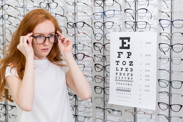 Attractive young woman wearing eyeglasses standing neat snellen chart in optica Free Photo