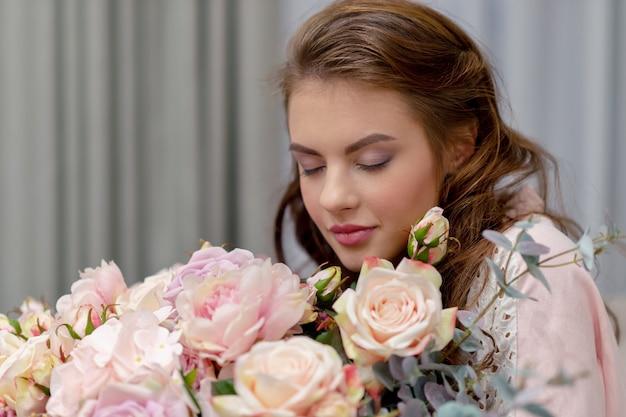 Attraente giovane donna con bouquet di centinaia di fiori sta trascorrendo del tempo a casa. Foto Gratuite