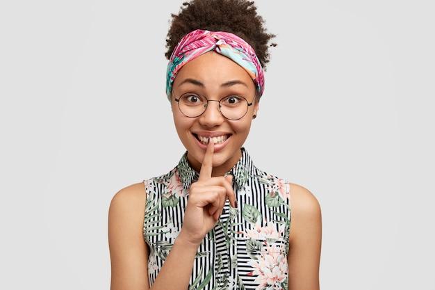 Attraente giovane donna con pelle scura pura, espressione positiva, fa il gesto di silenzio e dice shh Foto Gratuite