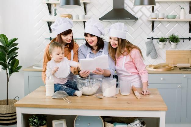 魅力的な若い女性、中年女性、かわいい娘がキッチンで調理しています。ケーキやクッキーを作りながら一緒に楽しんでください。女性はレシピ付きの料理本を読んでいます Premium写真