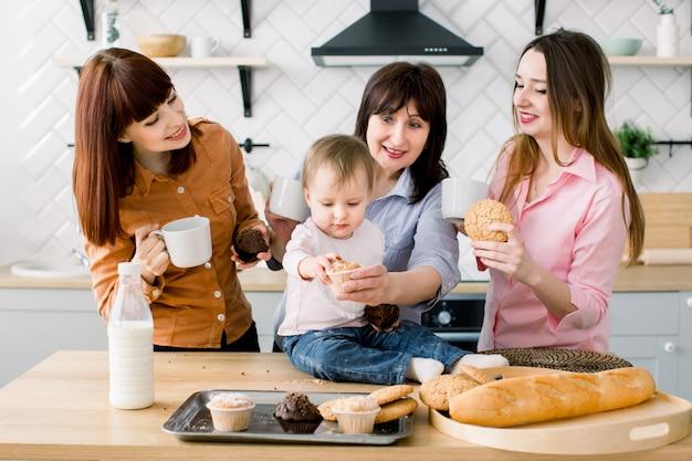 魅力的な若い女性、中年女性、かわいい娘がキッチンで調理しています。台所でマフィンを食べてコーヒーを飲む愛情のある家族 Premium写真