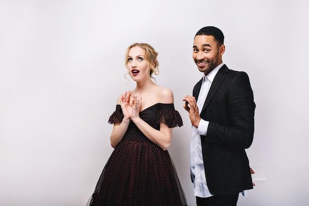 Привлекательная молодая женщина в роскошном вечернем платье с красивым мужчиной в смокинге с подарком за его спиной. шаловливая милая парочка, Бесплатные Фотографии