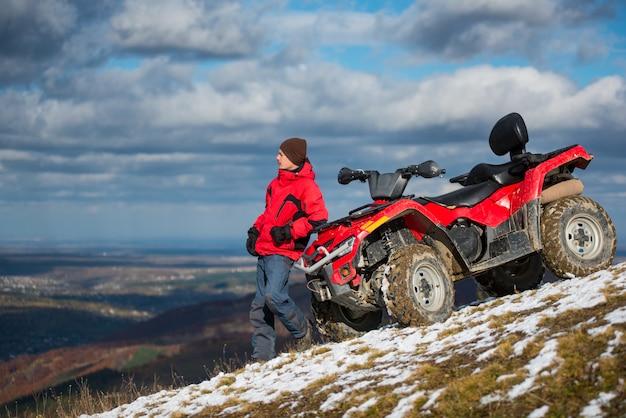 Atv quad bike near man on snowy mountain slope Premium Photo