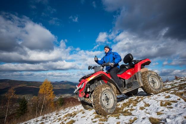 山で休んでいると親指を現してatvオフロード車の男 Premium写真