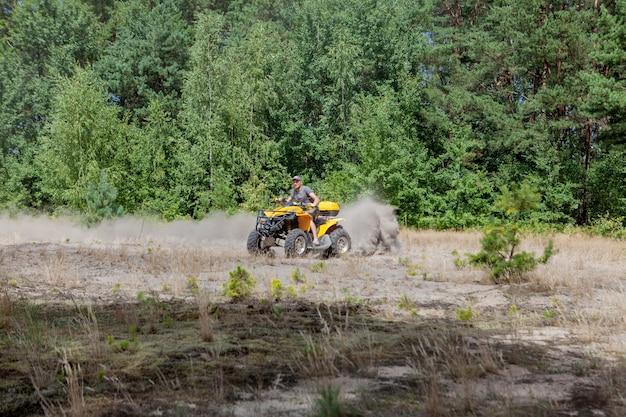砂の森で黄色のクワッドatv全地形車両に乗る男。極端なスポーツモーション、冒険、観光名所。 Premium写真