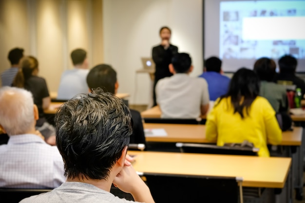 Audience listening speaker who standing in front of the room Premium Photo