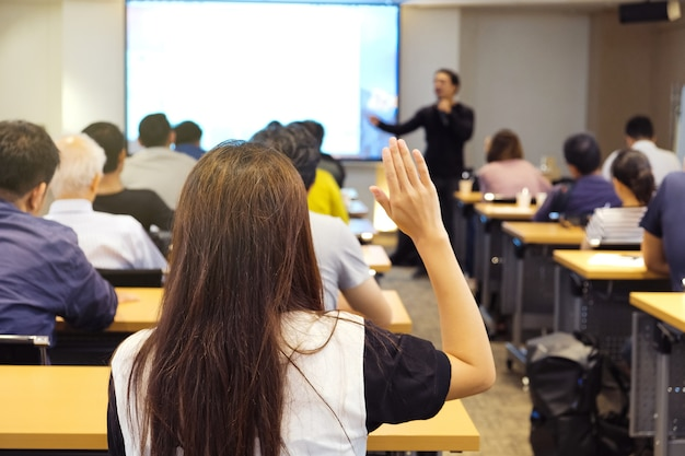 Audience raising hand up and listening speaker who standing in front of the room Premium Photo