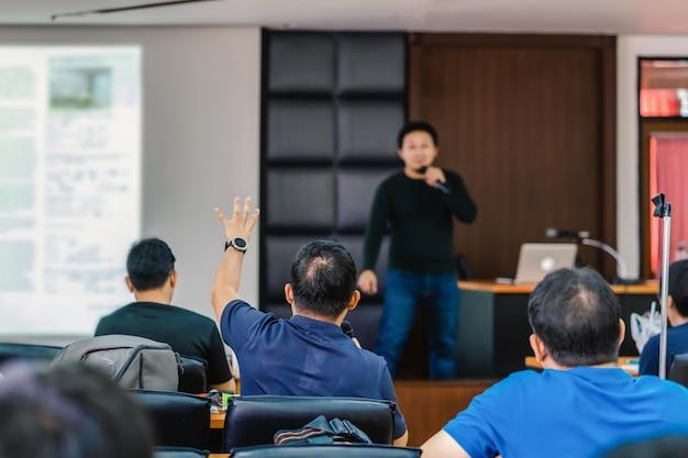 ステージ上のスピーカーからの質問に答えるために手を示す聴衆 Premium写真