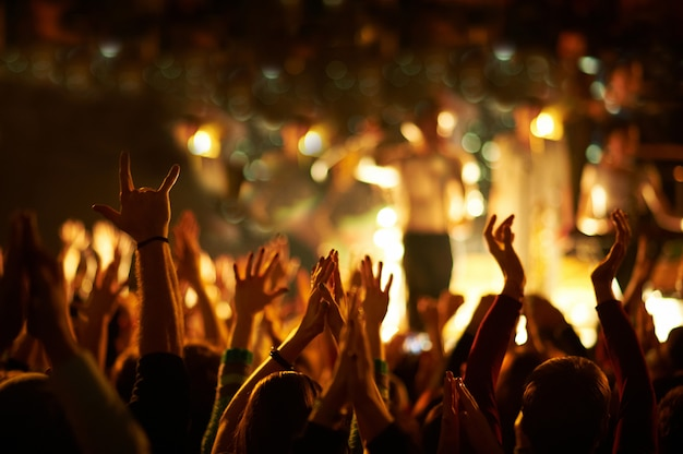 Audience with hands raised at a music festival and lights streaming down from above the stage. Premium Photo
