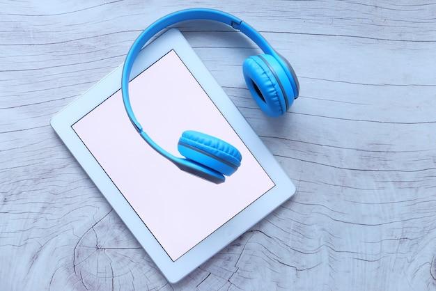 Концепция аудиокниги. наушники и цифровой планшет на столе Premium Фотографии