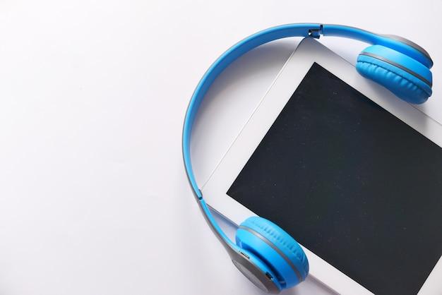 Концепция аудиокниги. наушники и цифровой планшет на столе. Premium Фотографии