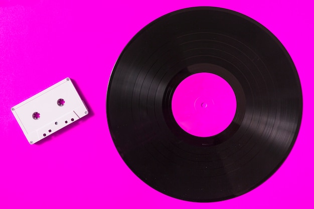 Audio white cassette tape and vinyl record on pink background Free Photo