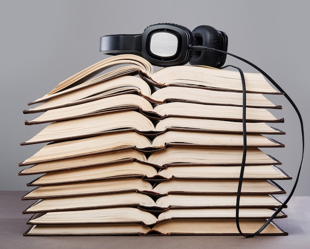 Audiobooks, headphones on book pile Premium Photo