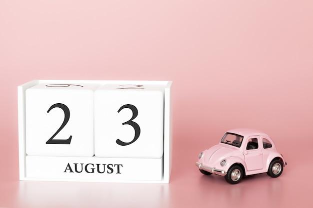 August 23rd, day 23 of month, calendar cube on modern pink background with car Premium Photo