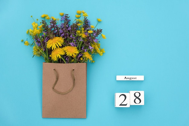 August 28 and field colorful flowers in craft package on blue background. greeting card Premium Photo
