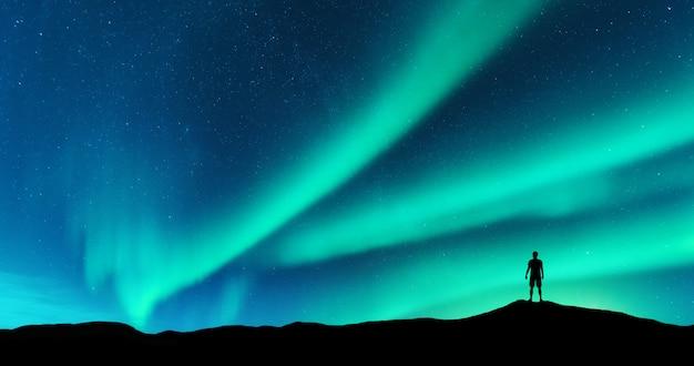 오로라와 언덕에 혼자 서있는 남자의 실루엣. Lofoten 섬, 노르웨이. 오로라 보리 얼리 스와 젊은이. 별과 녹색 극 빛으로 하늘입니다. 프리미엄 사진
