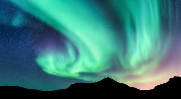 오로라 보 리 얼리스와 산의 실루엣 프리미엄 사진
