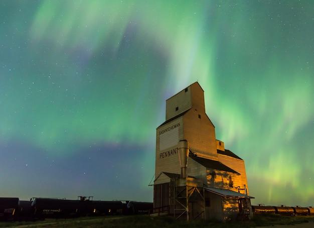 Aurora borealis over a historic grain elevator in pennant, saskatchewan, canada Premium Photo