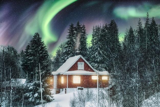 スカンジナビアの冬に雪で覆われた赤い北欧の家の上のオーロラ Premium写真