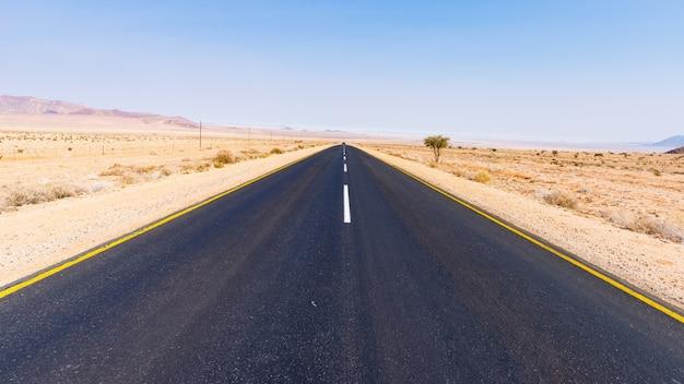 Дорога aus luderitz, пересекая пустынный ландшафт, намибия, африка. Premium Фотографии