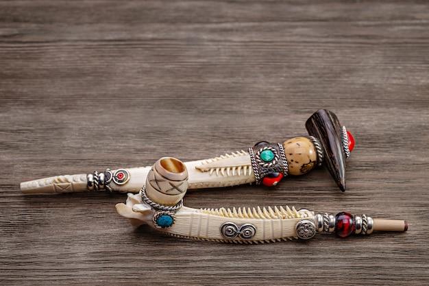 나무 배경에 뼈로 만든 담배에 대한 정통 상감 파이프. 아메리카 원주민의 엄숙한 파이프. 공간을 복사하십시오. 프리미엄 사진