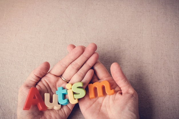 Autism colorful word on hands, wolrd autism day, april autism awareness month Premium Photo