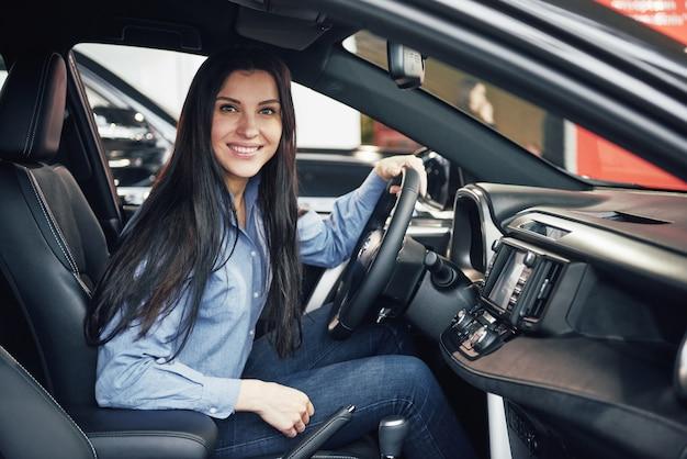 自動車事業、車の販売、消費者と人々のコンセプト-モーターショーやサロンでディーラーから車を取って幸せな女 無料写真