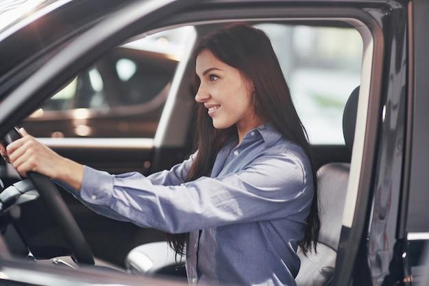 自動車ビジネス、車の販売、消費者と人々のコンセプト-モーターショーやサロンでディーラーから車のキーを取って幸せな女 無料写真