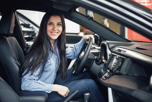 Auto business, car sale, consumerism and people concept - happy woman taking car from dealer in auto show or salon Free Photo
