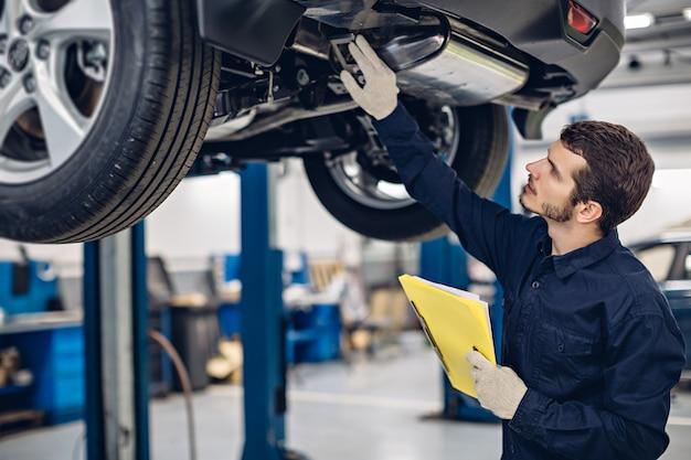 Auto car repair service center. mechanic examining car Premium Photo