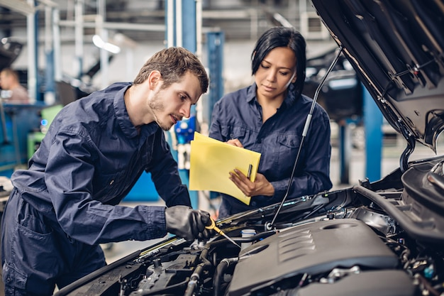Auto car repair service center. two mechanics - man and woman examining car engine Premium Photo